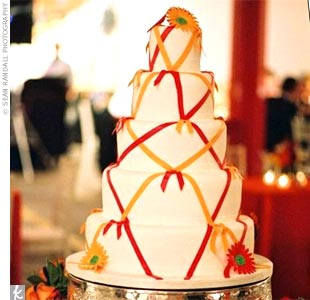 The cake was a five-tiered fondant-covered pound cake adorned with crisscrossing red and orange fondant ribbons and fondant gerbera daisies.