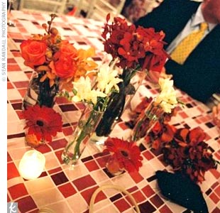 "Square tables were scattered around the dance floor. Orange linens with sheer, white-checkered overlays were topped off with scattered votive candles and three or four vases filled with different types of red, orange, and yellow blooms. ""It really was magical looking,"" the bride says."