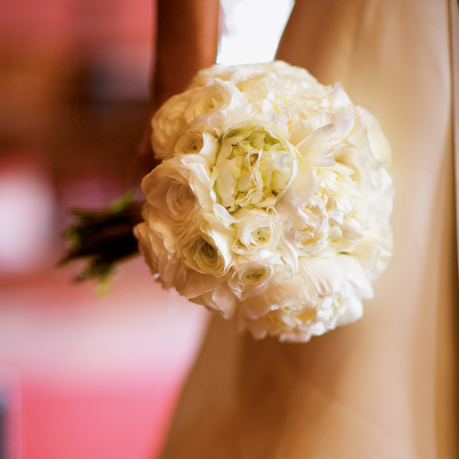 The bridal bouquet consisted of Annie's favorite flowers -- white peonies and ranunculus -- and was hand-tied with the same sable ribbon used on her gown.