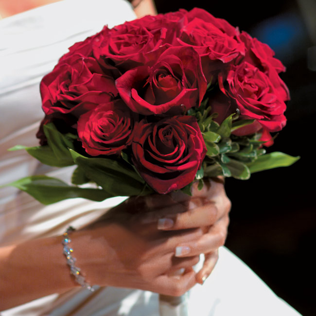 Nicole carried a bouquet of deep red roses adorned with gold glitter and tied with coordinating fabric from the gown.