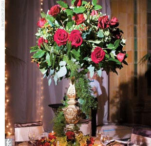 At the reception, each table was topped with a gold satin tablecloth and an arrangement of red roses.