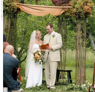The couple exchanged vows in a clearing of the orchard beneath a handcrafted wrought-iron huppah.