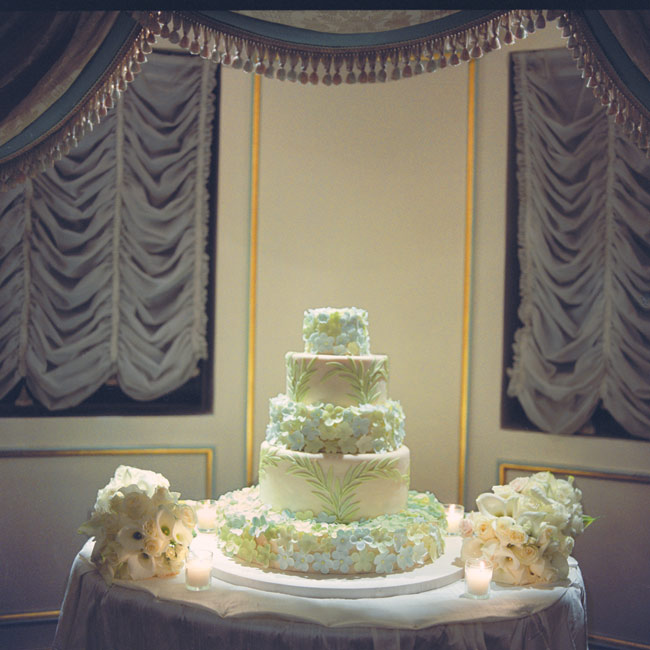 Five tiers of lemon pound cake filled with raspberry jam and covered in lemon buttercream were embellished with green and blue flowers to match the wedding colors.