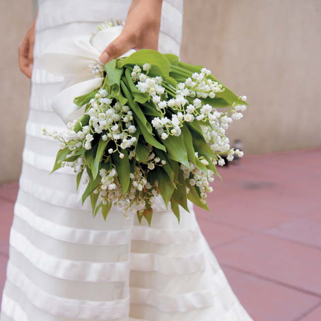 Elizabeth carried a bouquet of lily of the valley, a striking contrast to her all-white ensemble.