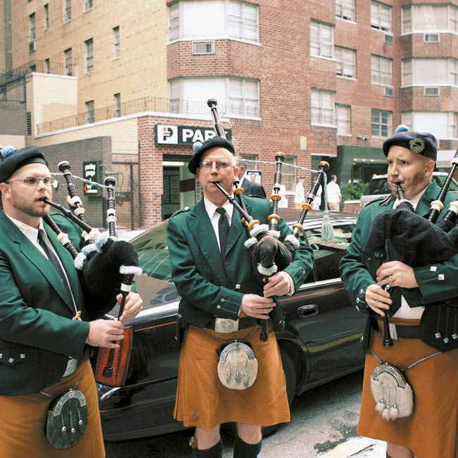 "Following the nuptials, Elizabeth and Kevin exited the church amid the sounds of bagpipers. ""They attracted a crowd of locals and people watching from their apartment windows,"" says Elizabeth. ""It was pretty cool."""