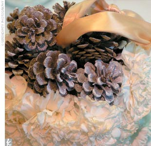 The flower girl carried a pomander of ivory carnations dotted with pinecones and held by a champagne-colored ribbon.
