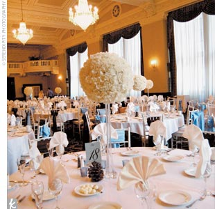 "Blue table cards were set in perfect brown on each table, and ""snowballs"" of carnations held aloft on glass towers alternated as centerpieces with glass bowls filled with and blue carnations."