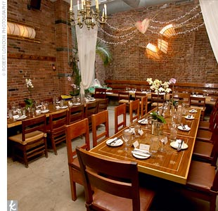 Rather than bringing in lots of decorative accents, Maggie and Jake decided to let the restaurant's natural beauty speak for itself. Three tables were set up beneath a skylight for the couple's 32 guests, and each table was topped with two orchid plants. A heart-shaped chandelier provided the room's warm, romantic lighting.