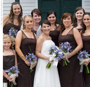Liz's seven bridesmaids wore short, brown dresses from After Six. Her junior bridesmaid wore a brown dress with a blue sash from Watters' WaWa line.