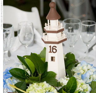 Hand-painted brown lighthouses numbered Liz and Jason's reception tables. The lighthouses were adorned with blue hydrangeas, Queen Anne's lace, and greenery.