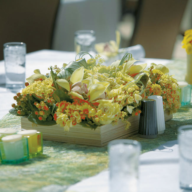Green natural-fiber fabric covered the reception tables, and floral arrangements in various shades of green sprung from square and rectangular bamboo bowls.