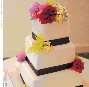 Guests enjoyed a three-tiered square cake decorated in white with ribbon bands around each layer and accented with bright flowers for a hint of color.