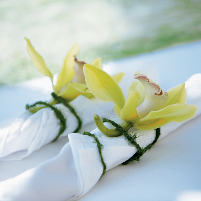 The flatware was rolled up into crisp white napkins and then tied off and finished with fresh orchids.