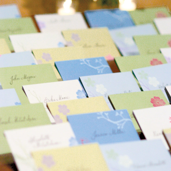To reflect the earthy tones of the wedding's mountain setting, Stephanie chose escort cards in shades of blue, green, white and yellow, which she hand-stamped with a nature-inspired motif.
