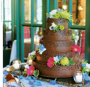 Stephanie and Greg cut into a five-tiered chocolate cake iced with chocolate buttercream and adorned with fresh flowers.
