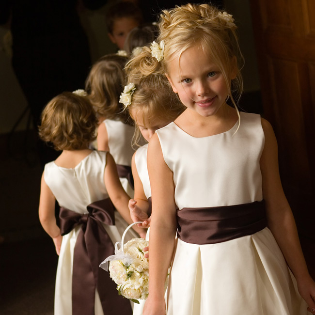 The entire bridal party complemented the wedding's overall look, with the flowers girls dressed in ivory dresses with chocolate-brown sashes, and the maids in strapless, dark chocolate-brown dresses.