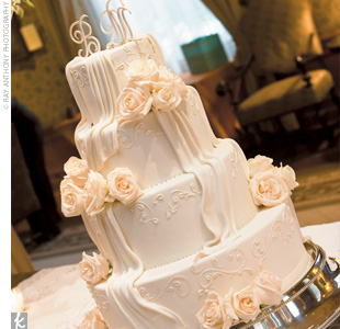 The four-tiered confection, which was frosted with vanilla buttercream, was decorated with ivory roses and topped with the couple&#39;s monogram.