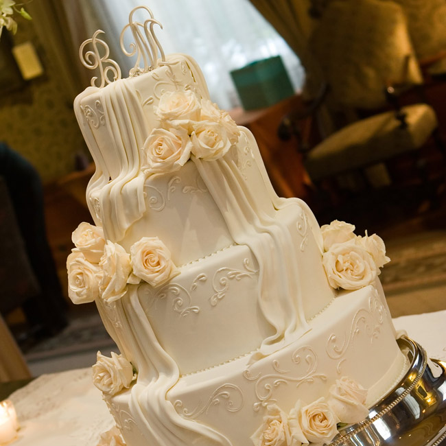 The four-tiered confection, which was frosted with vanilla buttercream, was decorated with ivory roses and topped with the couple's monogram.