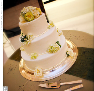 Guests were treated to a three-tiered, white chiffon and chocolate mousse cake. The confection was decorated with fresh green and ivory flowers and served with a raspberry sauce. The cake was cut and served at a dessert bar complete with crystal sugars, cinnamon sticks, bittersweet chocolate shavings, sugared orange and lemon rinds, and whipped cre ...