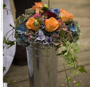 Shepherd's hooks hung with galvanized buckets filled with orange roses, burgundy dahlias, and cascading purple hydrangeas decorated the ceremony site.