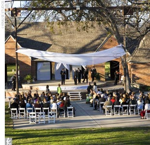 Dori and Jason married in an outdoor ceremony at sunset in the Shakespeare in the Park Amphitheater. The couple stood on the stage that's used for summer festivals, while their guests sat before them in chairs set up on the grassy lawn.