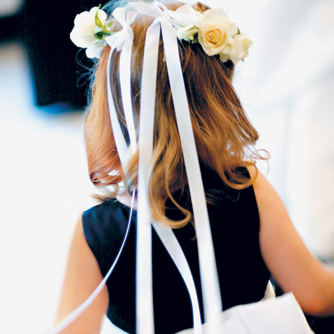 In keeping with the colors of the day, the flower girl wore a sleeveless black dress teamed with a white sash.