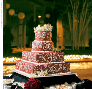 The four-tiered creme brulee confection featured lace-like scroll-work atop merlot-colored fondant.