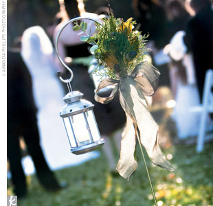 Ashley and Jeremy's guests formed a circle around them as they said their vows outdoors underneath the tall oak trees. The main aisle was marked with shepherd's hooks tied with wheat, berries, and ribbon. And as each bridesmaid walked down the aisle, she placed a lantern on one of the hooks -- one of Ashley's favorite parts of the ceremony.