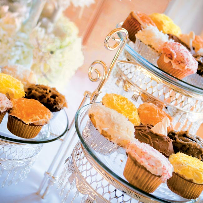 """""""We always wanted cupcakes for our wedding cake,"""" Ashley says. Jeremy's mother baked over 200 cupcakes (flavored strawberry, red velvet, chocolate, vanilla, and confetti), and the couple displayed them on tiered dessert stands accented with hanging crystals."""