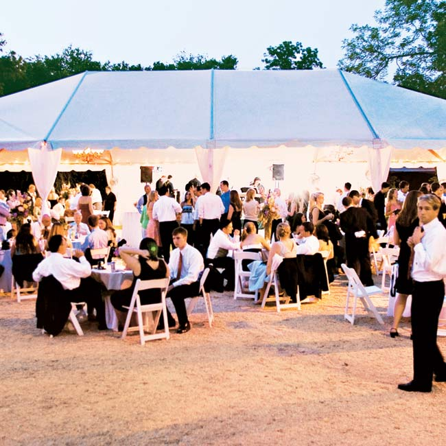 Following the intimate ceremony (the groom's father officiated), large wrought-iron candelabras lit the way for guests to walk from the ceremony to the reception tent behind the house.