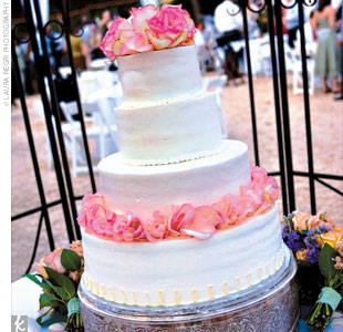 Following dinner, the couple cut into their four-tiered, round, Spanish lemon cake with buttercream icing, which was covered with rolled pink rose petals.