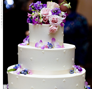 The couples florist decorated the cake with pink and purple blooms to match the weddings color palette. The white cake was frosted with buttercream and included raspberry filling.