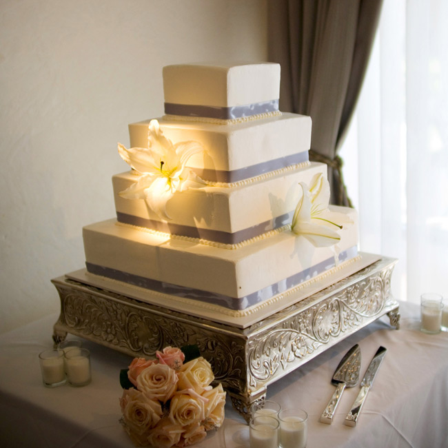 Each layer of the four-tiered, square, white cake was lined with silver ribbon and was made of a different flavor: strawberry shortcake, chocolate Parisian, carrot cake, and Cuban vanilla.
