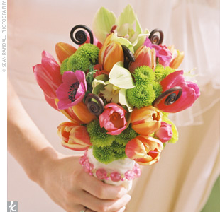 The brides brightly hued bouquet consisted of fuchsia ranunculuses and anemones, fuchsia and mango-colored tulips, chartreuse cymbidium orchids, lime Kermit mums, and chocolate fiddlehead ferns.