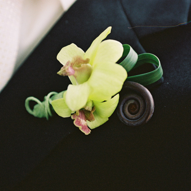 Dave wore a boutonniere made of two chartreuse dendrobium orchids accented by a chocolate-colored fiddlehead fern and loops of green lily grass.