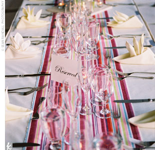 "The inspiration for the vibrant palette came from multi-colored table runners that Jennie had found. ""The bright, striped table runners were placed on top of simple ivory linens for a pop of color,"" Jennie says."