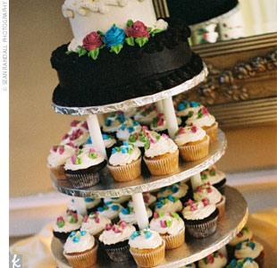 Although a tower of cupcakes in four flavors (carrot, banana, chocolate, and Italian cream) served as dessert, the couple included two cakes on the top tier so that they had one to cut and one to save.
