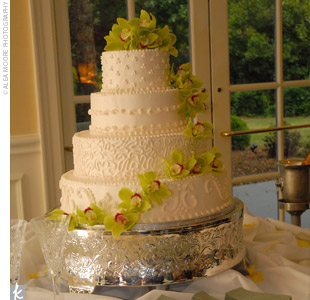 The four-tiered cake featured a different design on each layer, including polka dots and scrolling. The cake was iced with vanilla buttercream frosting and decorated with cymbidium orchids to continue the wedding's green color scheme.
