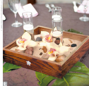 Zen-inspired centerpieces were created inside oak boxes, handmade by the brides brother. Pearl inlays in the shape of cherry blossoms added an ornate touch to the boxes, which were filled with candles, Japanese river rocks, and orchids.