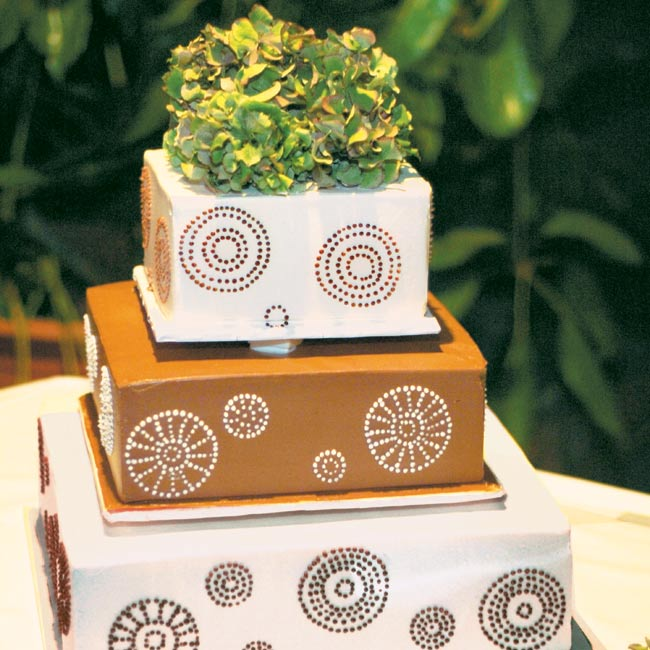 Kathleen and Alexander cut into their three-tiered, square, chocolate, brown-and-white iced cake.