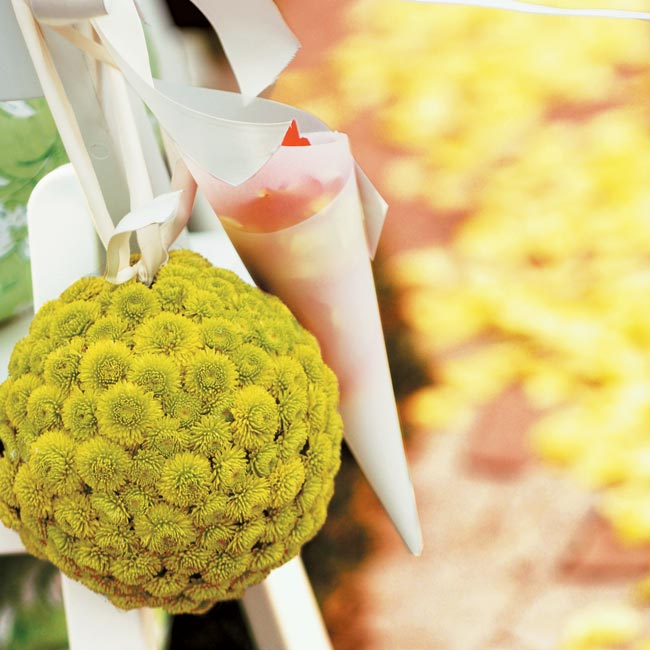 Kissing balls of green button mums hung from shepherd's hooks, while cones filled with orange, lime, and ivory rose petals hung from each aisle's end chair for guests to toss.