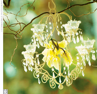 A dramatic candle chandelier adorned with large green cymbidium orchids hung over the couple as they exchanged traditional Christian vows.