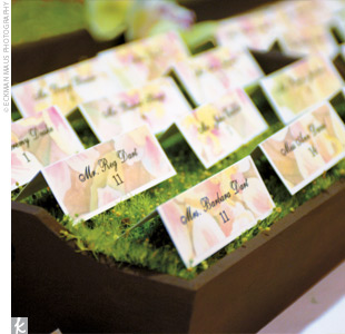 The ivory and floral vellum escort cards rested atop moss decorated with green orchids and glass votives.