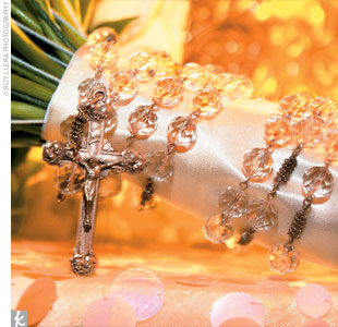 Small crystals sparkled from Maitee's bouquet, which was filled with green cymbidium orchids, cream roses, calla lilies, and stephanotis. An antique rosary and off-white satin ribbon held the blooms together.
