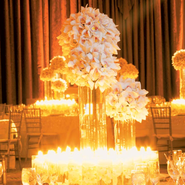 Two centerpieces added to the elegant decor. The first was created from three different-sized cylinder vases filled with water and topped with white cymbidium orchids, floating candles, and submerged dendrobium orchids.