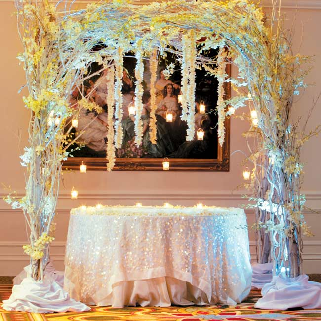 Guests picked up their escort cards from a table surrounded by huppah-style draping, decorated with white branches, hanging orchids, candles and dendrobium garlands.