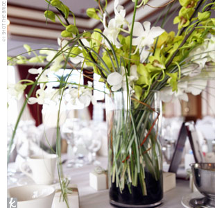 """Steve and I strove for simplicity when it came to the wedding,"" Ann says. ""We wanted simple flower arrangements so that the views of Miami were not obstructed."" Half the tables were set with centerpieces of white calla lilies set in low, square, glass vases filled with white stones, while the other half were green orchids and branches in round vas ..."