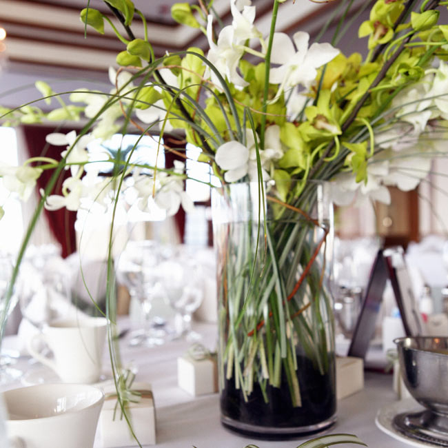 """""""Steve and I strove for simplicity when it came to the wedding,"""" Ann says. """"We wanted simple flower arrangements so that the views of Miami were not obstructed."""" Half the tables were set with centerpieces of white calla lilies set in low, square, glass vases filled with white stones, while the other half were green orchids and branches in round vas ..."""