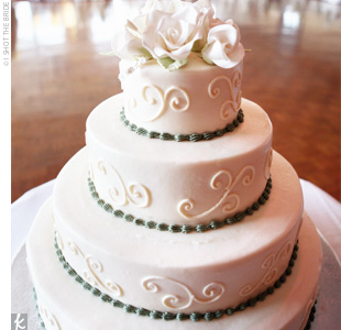 Ann and Steve cut into a four-tiered cake covered in ivory fondant. The cake was decked out with ivory swirls and sage green, beaded bands at each tier and then topped with fresh flowers.