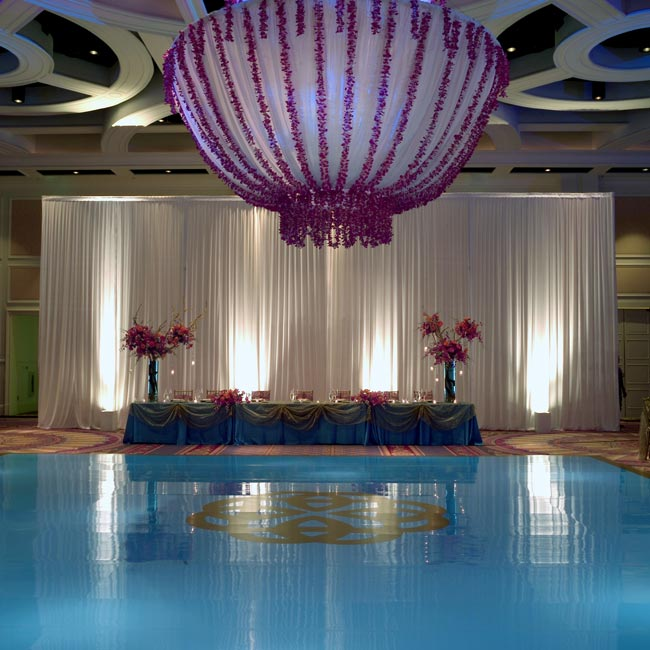 Joy and Sateesh had sent out invites in pink (for her family) and turquoise (for his), and they carried this vibrant color scheme into their reception. A twelve-foot chandelier of orchids hung above a turquoise dance floor with the couple's seal in the center.